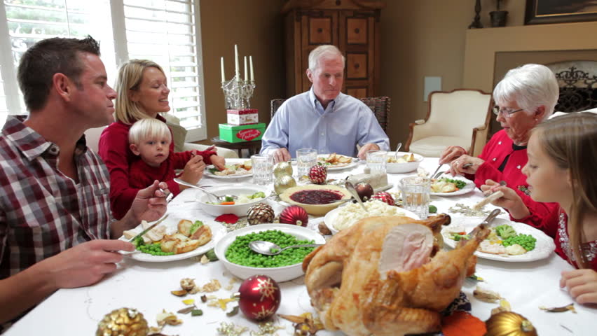 Camera tracks across table as extended family sit and enjoy thanksgiving dinner. Shot on Canon 5d Mk2 with a frame rate of 30fps