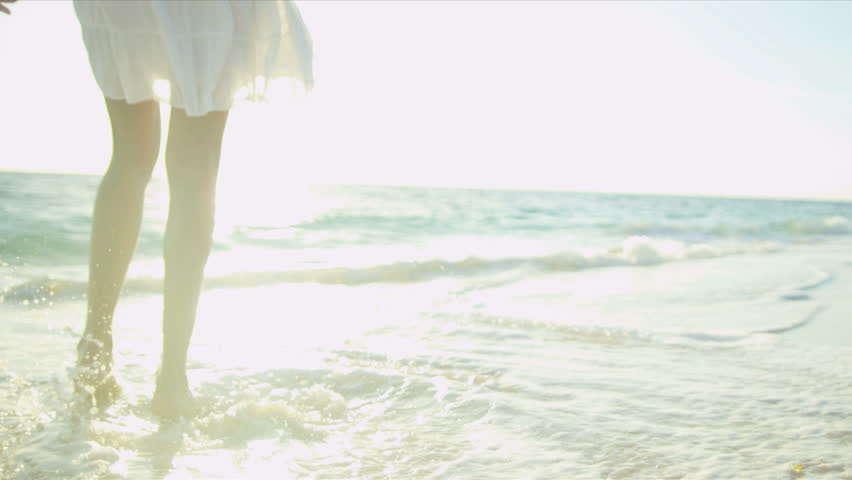 Legs feet Hispanic girl walking barefoot wet sand island beach sun lens flare shot on RED EPIC | Shutterstock HD Video #3789329