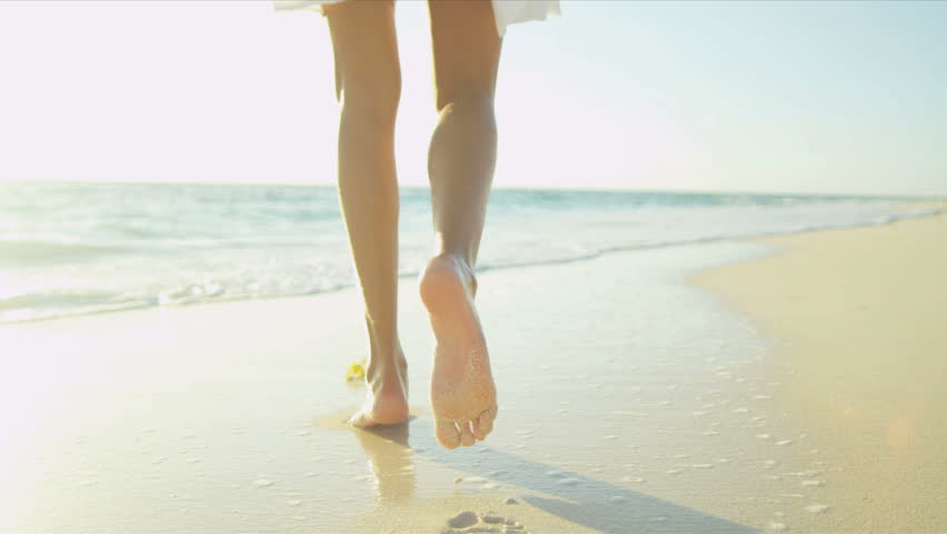 Bare legs feet young Latin American girl walking by ocean shallows sun lens flare shot on RED EPIC