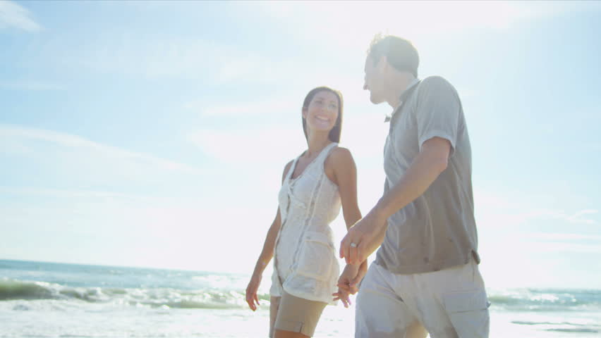 Loving young Caucasian couple holding hands walking together beach shot on RED EPIC