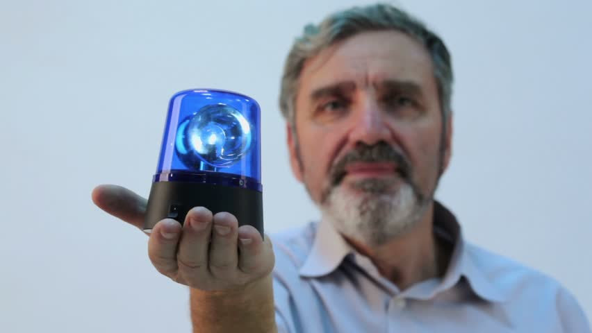 Senior man with beard holds blue blinker on hand, focus on flasher