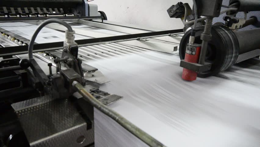 folding machine folds printed offset sheet as part of newspaper brochure in print house
