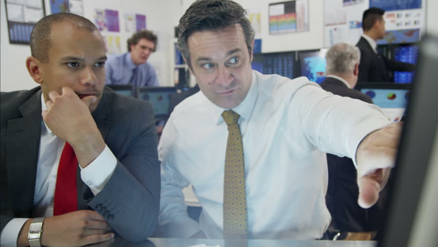 Two male financial traders are working in a busy office filled with computers. They are discussing market prices and profits, as the rest of their team are hard at work in the background.  #3807710