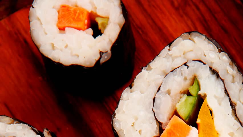 Japanese traditional Cuisine - Roll with Cucumber Cream Cheese with raw Tuna(maguro) and Salmon(sake) inside. on wooden plate with wasabi and ginger isolated over white background