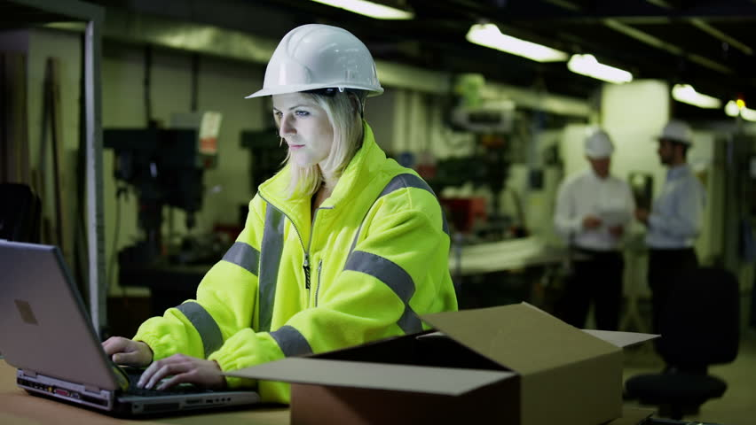Attractive female warehouse employee wearing high visibility clothing and a hard hat is working on a laptop computer and checking her stock. In slow motion. | Shutterstock HD Video #3817709