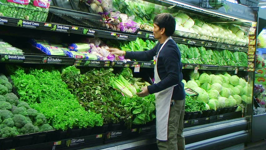 Worker facing  fresh vegetables in grocery store.