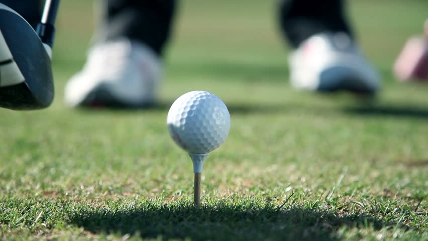 Close up shot of a golfers walk towards a point where he sticks a white golf ball on the special holder