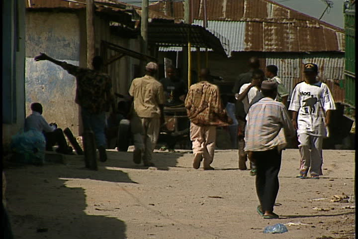 DAR ES SALAAM, TANZANIA - DECEMBER 1, 1998: Young men and boys walking on dirt road between buildings.
