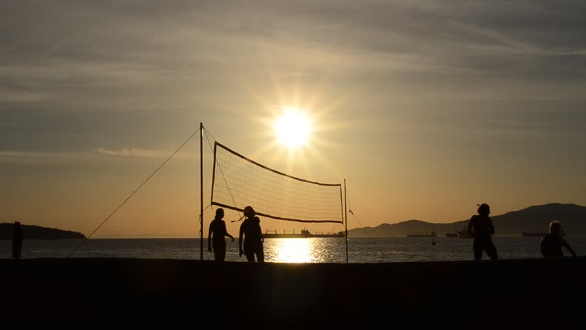 Playing beach volleyball at dusk