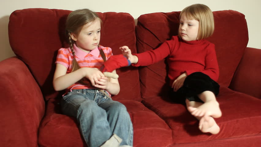 Sisters fighting - two young girls fighting over a toy doll