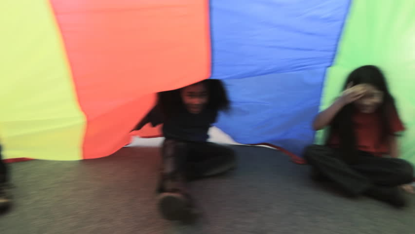 Parachute Silk - children sit and wave under a colorful parachute silk