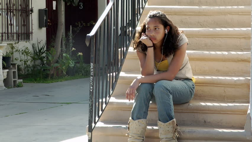 Wide shot of young ethnic teenage girl sitting on steps with headphones on sitting in deep thought leaning towards uncomfortable and depressed feelings being shown in her expression and body language.