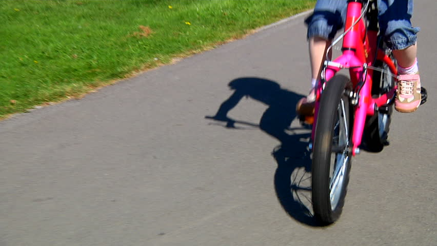 Little girl cycling in park - track along with her