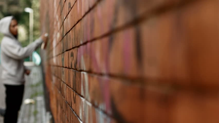 Teen spraying graffiti - teenage boy in hoody spraying graffiti onto a brick wall