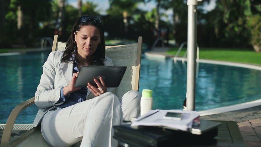 Successful businesswoman with tablet computer by the pool