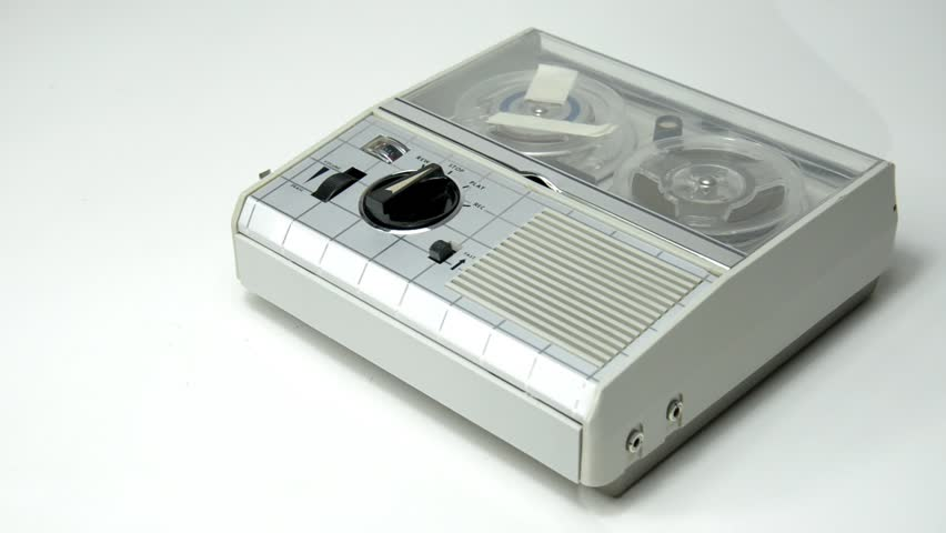 A hand starts and stops playing a reel tape on an old portable reel-to-reel mini tape-recorder.