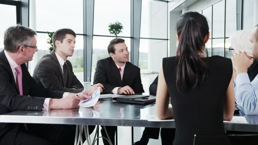 A confident and attractive business team of mixed ages and ethnicity are holding a meeting in a light, modern office building. They are discussing ideas for their business development. In slow motion. | Shutterstock HD Video #3870644