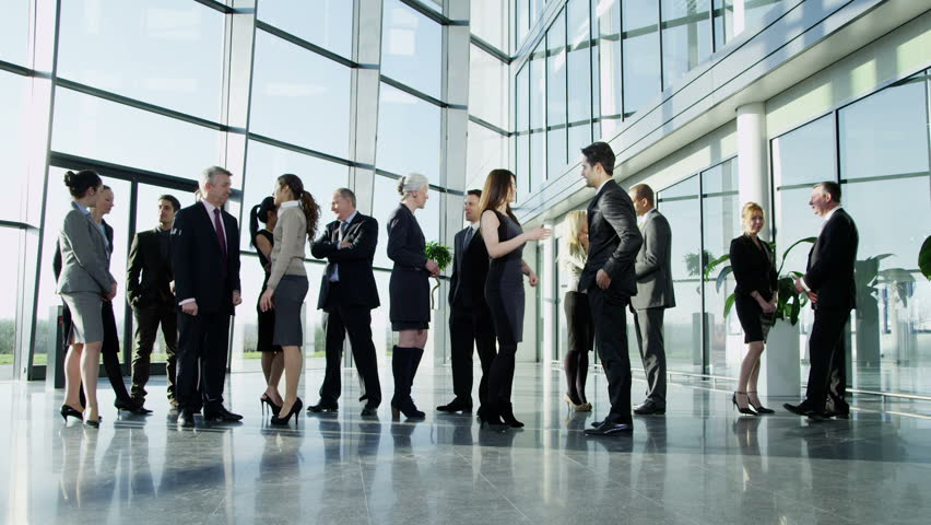 Diverse group of business people, stand and chat to each other in a light and modern glass fronted office building on a bright day. In slow motion. | Shutterstock HD Video #3872423