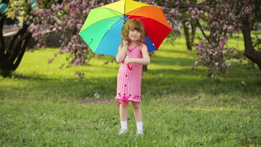 Kid Turnning The Umbrella And Smiling
