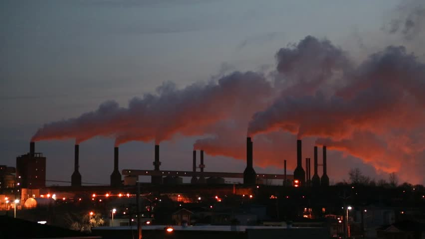The sun sets on an Aluminum plant, giving the smoke spewing from it a bright orange glow.