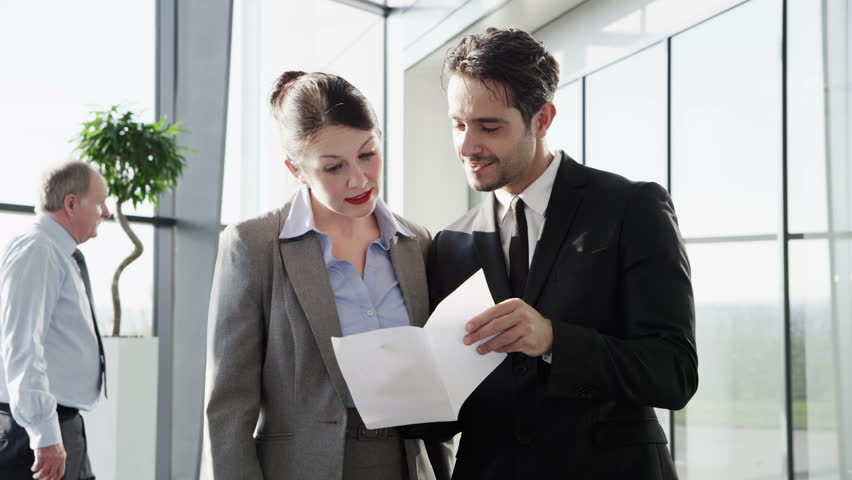An attractive young businessman and businesswoman meet to discuss a business contract in the lobby of a light and contemporary office building.