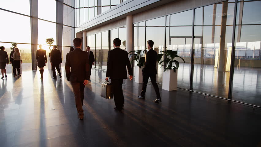 Two young businessmen who are old acquaintances, meet and shake hands in a busy modern office building at sunset.  | Shutterstock Video #3893477