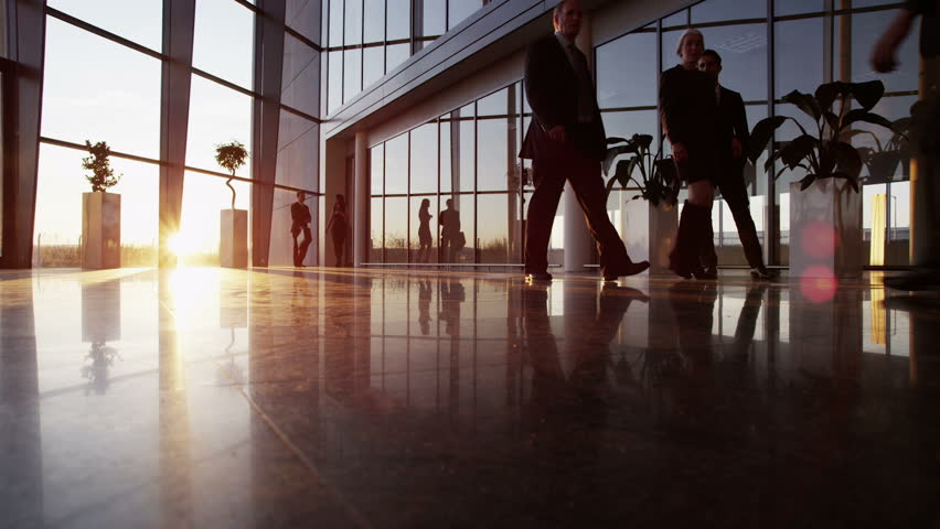A diverse group of business people are making their way around a busy modern office building as the sun sets outside. | Shutterstock HD Video #3893504