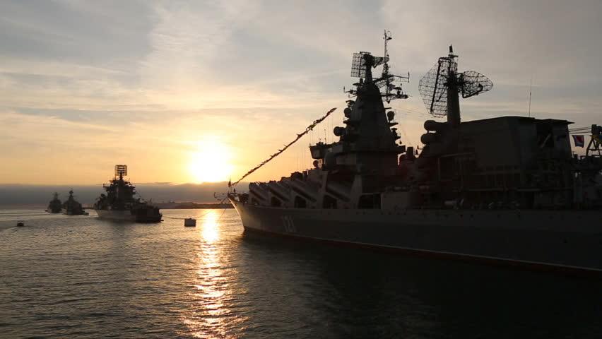 Warships at anchor in the bay at sunset