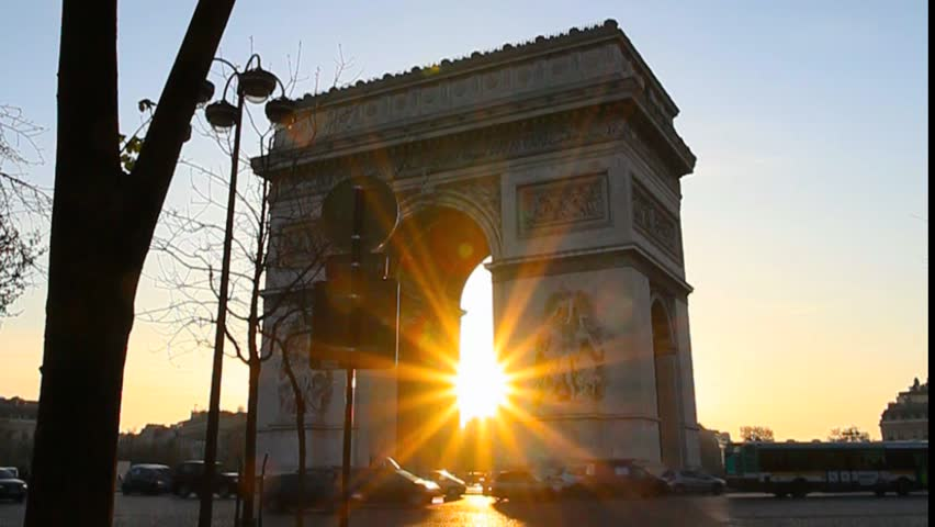 The sunrise peeks through the Arc de Triomphe in this springtime sunrise.  Numerous cars and buses bustle through the frame in silhouette.