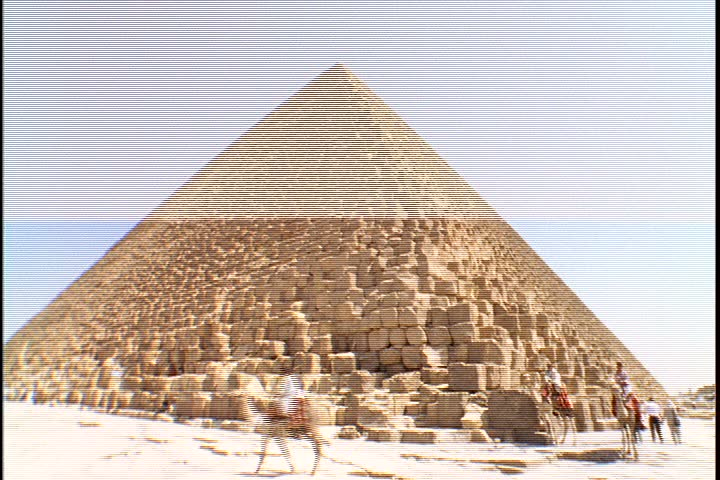Scenic shots of the Great Pyramids; WS of pyramid with a few men on camels nearby.