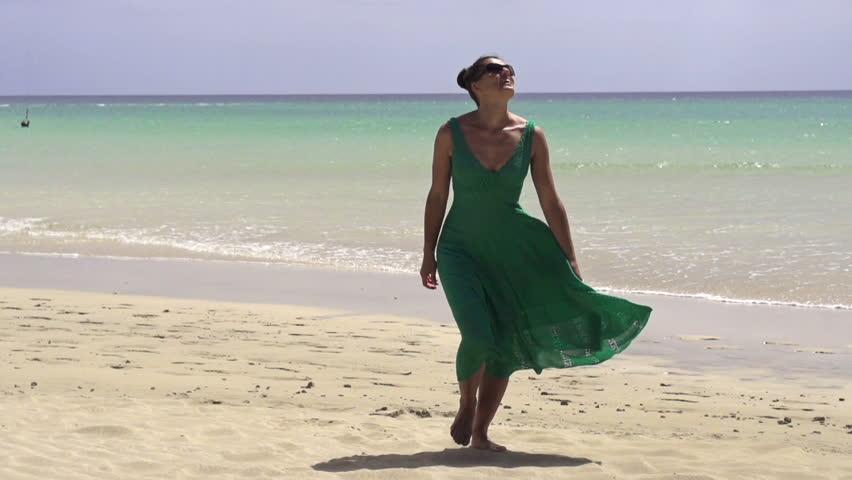 Happy woman in dress walking on the beach