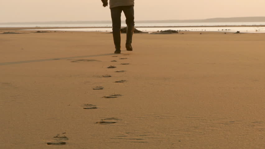 Man walking on the sand leaving his footprints