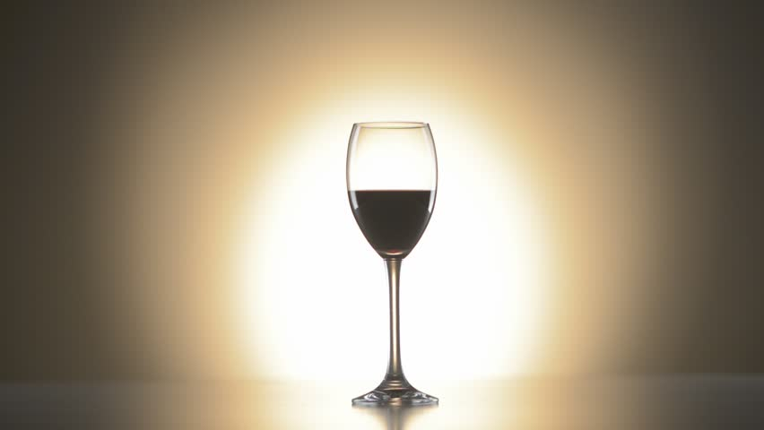 Wide shot of a wine glass with redwine and a bright spot in background fading up an down | Shutterstock HD Video #3957404