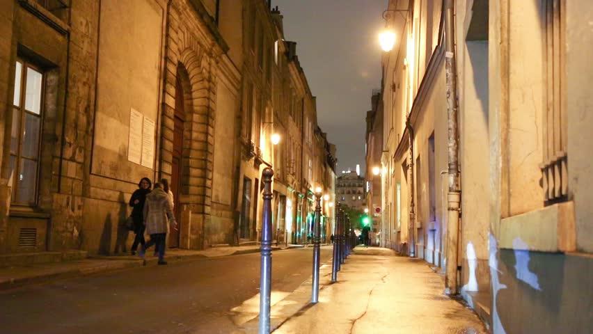 PARIS - NOVEMBER 11 2012: Vehicles drive through a narrow road as pedestrians walk on the sidewalk on November 11, 2012 in Paris, France.