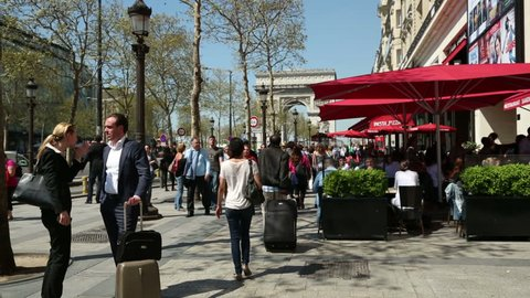 PARIS - APRIL 26: Unidentified people in Champs-Elysees walk past cafes and restaurants on April 26, 2013 in Paris. Champs Elysees and Arc de Triomphe are major tourist attractions.