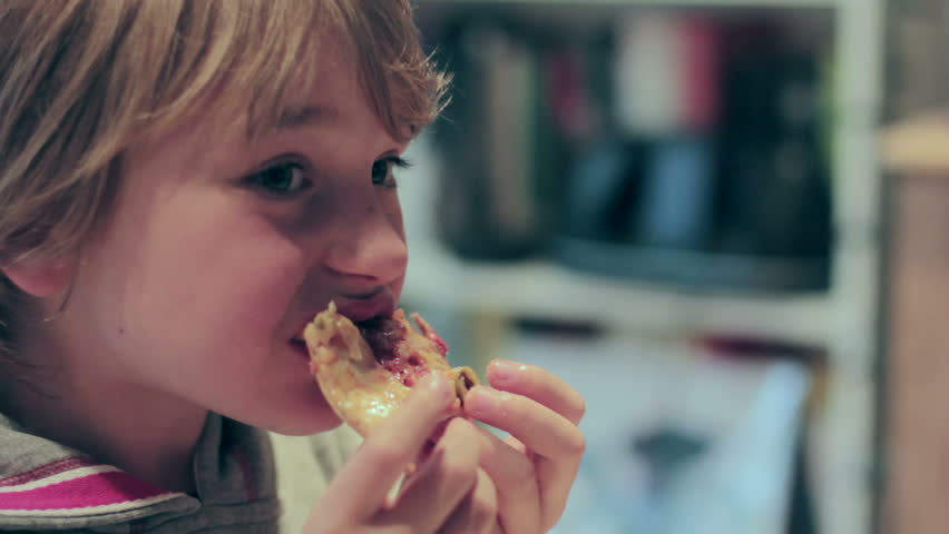 A young boy devours a pizza slice.
