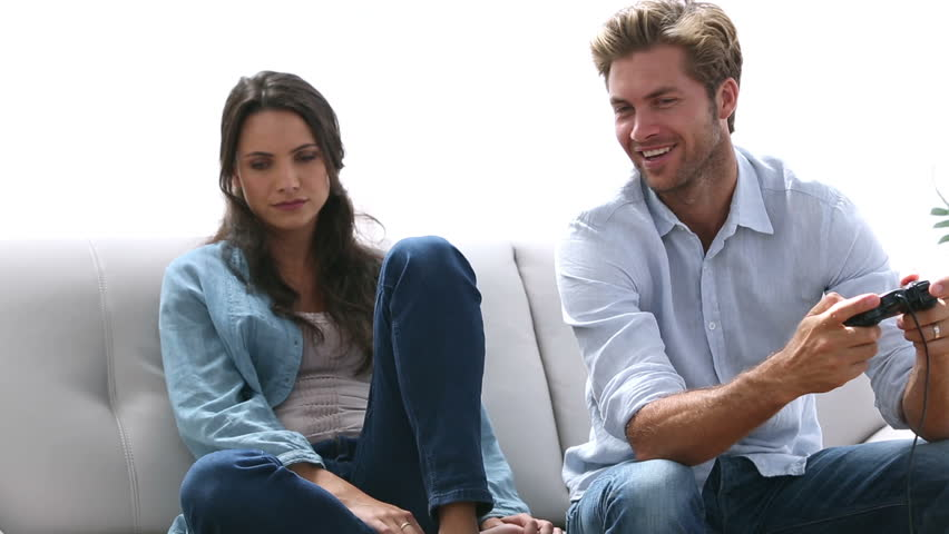 Woman annoyed by her partner playing video games at home on the couch