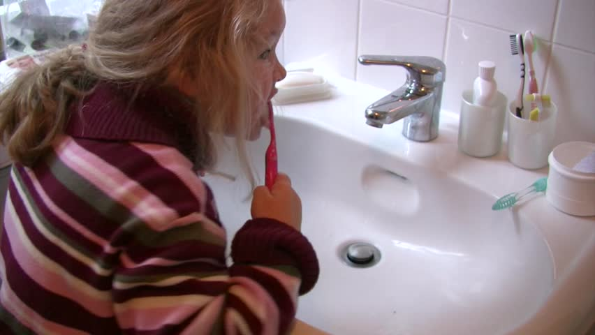 Young Girl brushing teeth at domestic sink