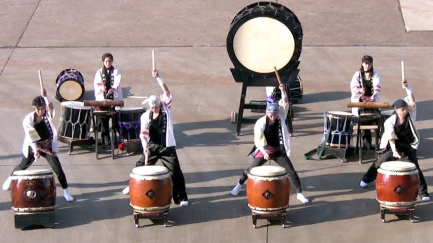 MIYAZAKI, JAPAN - MARCH 30, 2010: At sunset the group of unidentified four men and two women in the Japanese national costume play the Japanese national drums. Slow motion