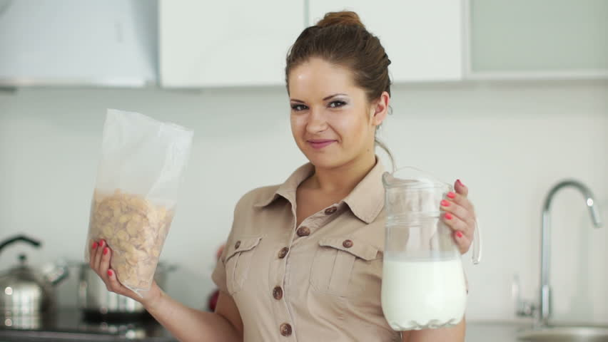Girl standing in kitchen and holding package with cornflakes and milk carafe
