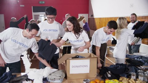 Attractive young charity volunteers are sorting through clothing which has been donated by the people of the local community. In slow motion.