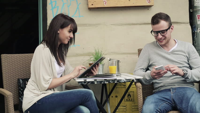 Happy couple with smartphone and tablet in cafe,...