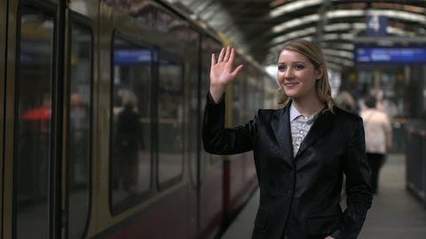 woman saying goodbye in train station. bye bye. female person people