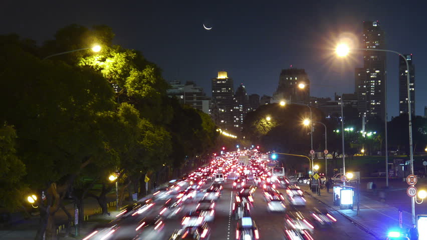 Traffic in the city. Avenue Time-Lapse, Night. Moon going down. Heavy traffic / jam / flowing with blurred motion. Dusk. Crane out / zoom.