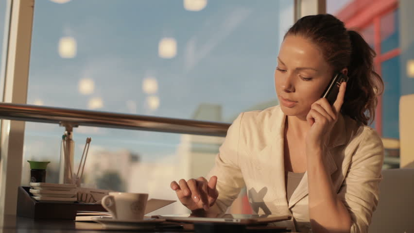 beautiful young woman sitting at a table in a cafe, she works with the tablet, talking on the phone and making notes in a notebook. Then stretches his neck and drinks coffee. she was tired