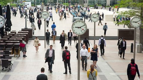 LONDON - JUNE 04:  Business people going to work in Canary Wharf, the financial district of London. 04 June 2013, England.