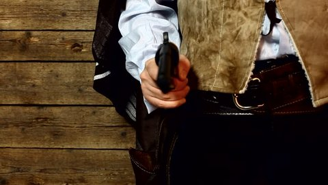 Gunslinger pulls out the gun on wooden background. dolly shot.