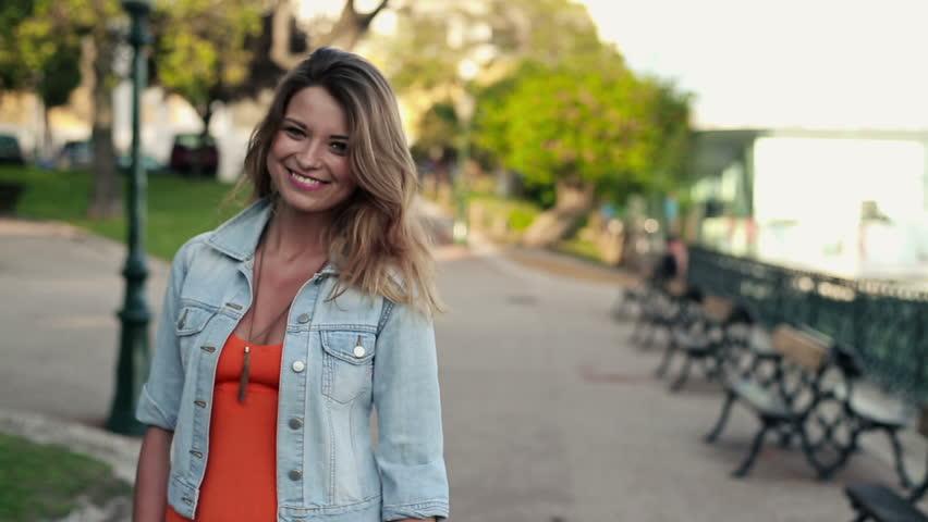 Happy beautiful woman walking in the city, steadicam shot