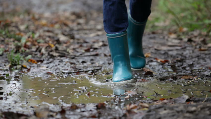 stock video clip of rain boots walking in mud puddle and