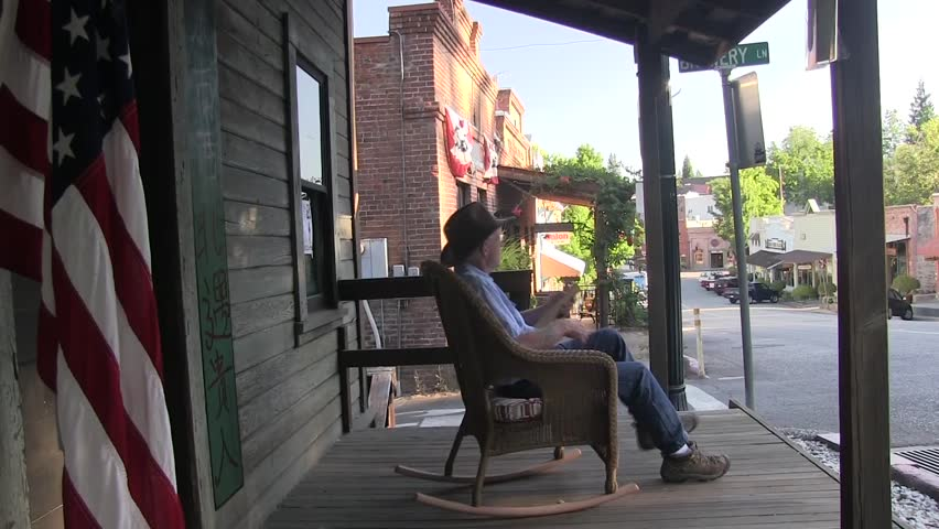 Old Small Town America Man Whittling Sitting On Rocking Chair. American  Flag On Sidewalk And